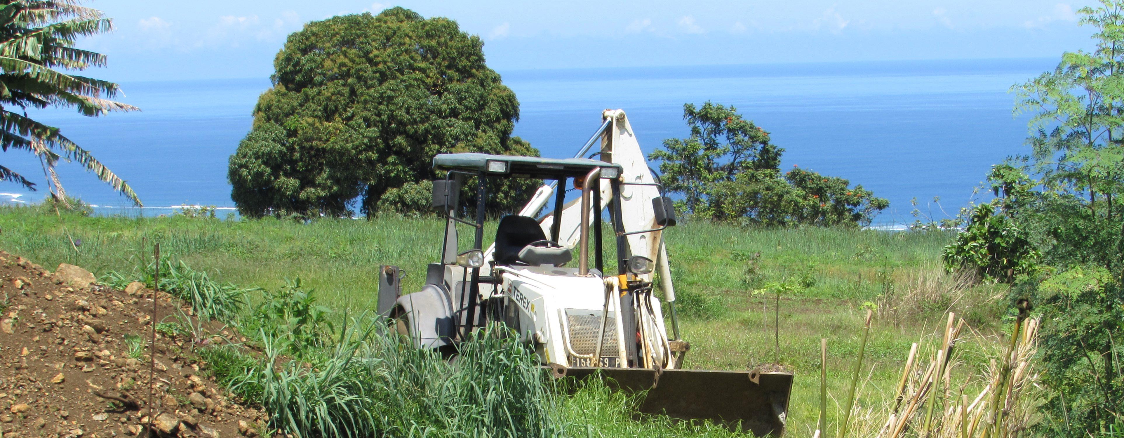 Tracteur blanc en service dans un champ, en hauteur.